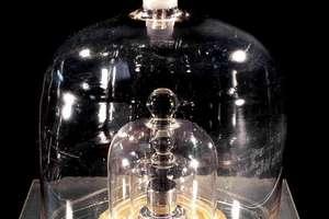 """""""Marele K"""" - unitatea care defineste kilogramul este un cilindru conservat sub trei clopote de sticla, în regiunea pariziana. Aici este o replica aflata în Cité des Sciences."""