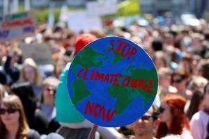"""Pe o parcarta se poate citi """"opriti schimbarile de mediu acum""""."""