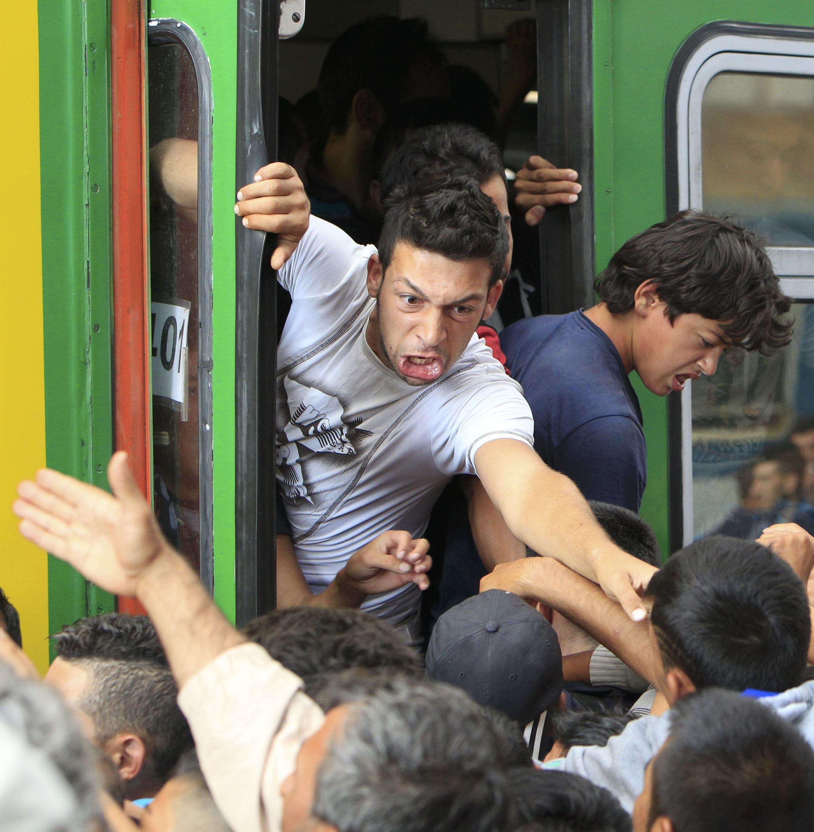 Încăierare între imigranţii care vor să prindă un loc pe scara unui tren (Foto: Reuters/Bernadett Szabo)