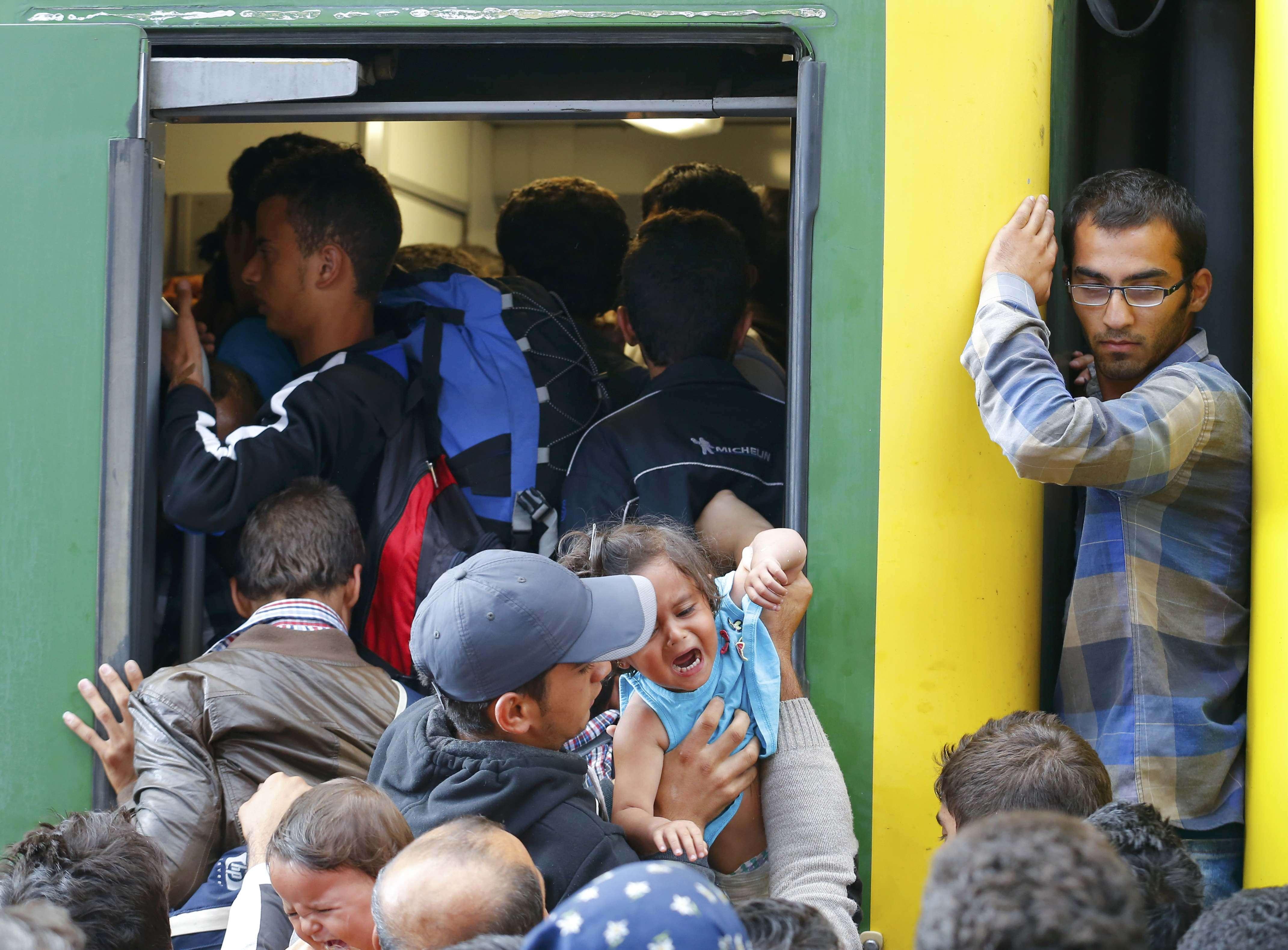 Orice loc e bun în trenul imigranţilor, chiar şi între vagoane (Foto: Reuters/Laszlo Balogh)