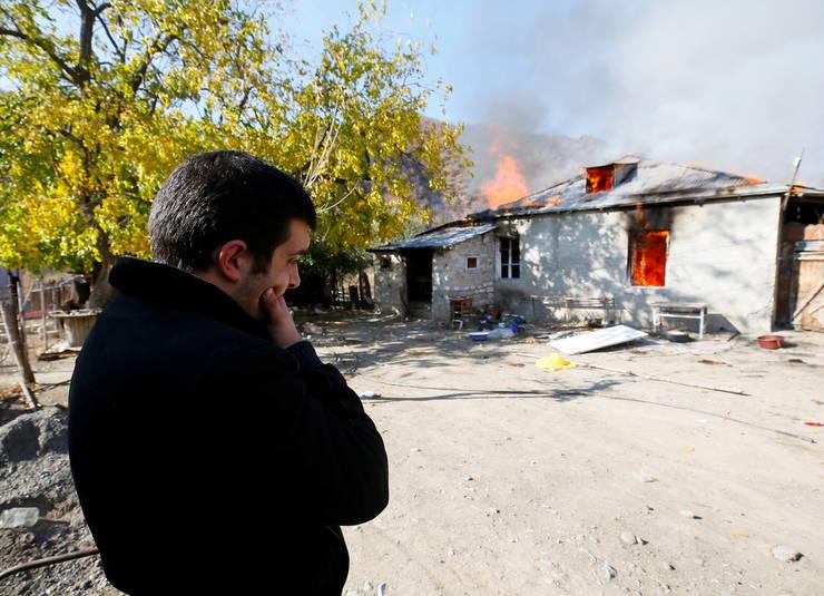 Un bărbat armean stă lângă o casă incendiată în satul Cherektar, în regiunea Nagorno-Karabakh