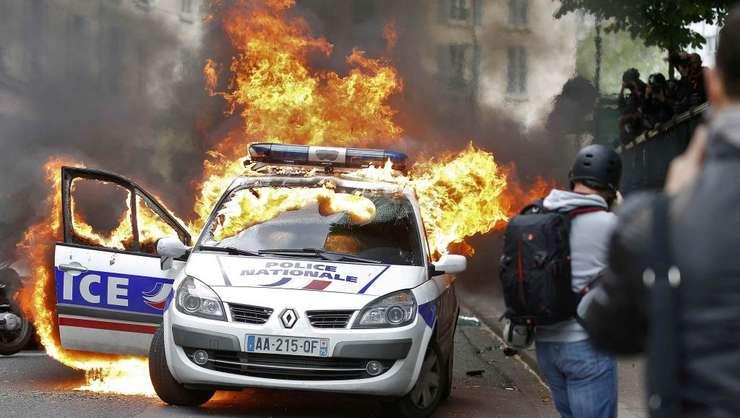 """Maşină a poliţiei incendiată de manifestanţi pe 18 mai 2016 în Piaţa Republicii la Paris în contextul unei manifestaţii """"împotriva violenţelor polţieneşti"""" interzisă de prefectură."""