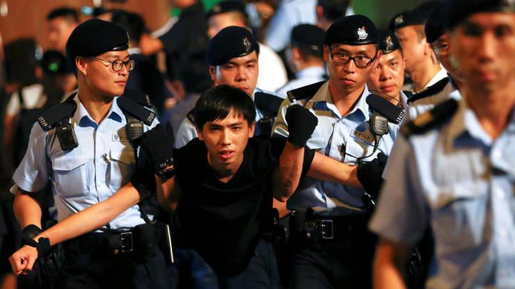 Militant prodemocraţie arestat în timpul unei manifestaţii la Hong Kong.