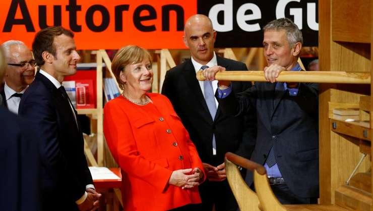 Emmanuel Macron si Angela Merkel la standul francez de la Tîrgul de carte de la Frankfurt