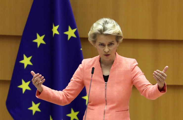 Președintele Comisiei Europene, Ursula von der Leyen, la microfonul tribunei Parlamentului European, cu un taior roz, cu steagul Uniunii Europene in background pe partea stanga.