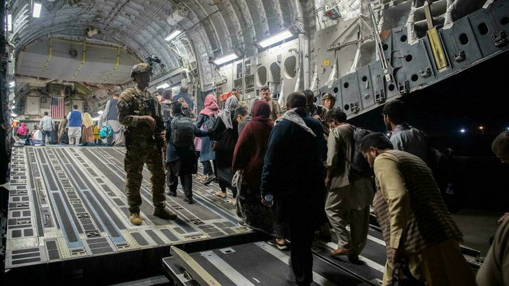 Afgani urca la bordul unui avion de transport al US Air Force pentru a fi evacuati, Aeroportul Hamid Karzai din Kabul, 22 august 2021. Franta opreste evacuarile dacă SUA se retrag, asa cum era prevăzut, pe 31 august.