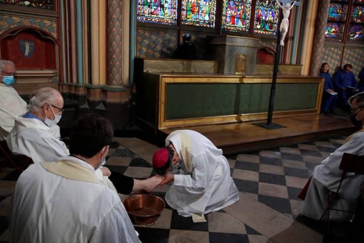 Arhiepiscolul Parisului, Michel Aupetit spala picioarele unor persoane în cadrul unei ceremonii religioase derulate în joia de dinaintea Pastelui catolic, 1 aprilie 2021, catedrala Notre Dame, Paris.