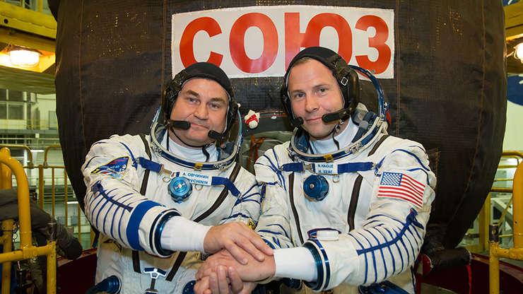 Aleksey Ovchinin (s) şi Nick Hague (d), în faţa capsulei Soyuz (Sursa foto: site NASA)
