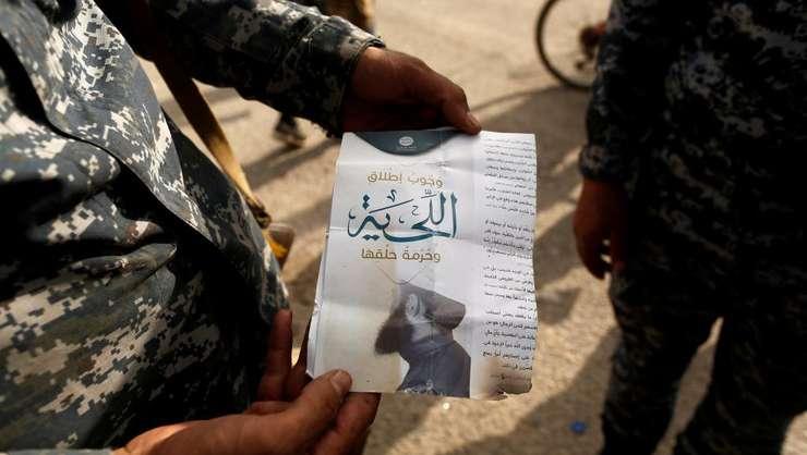 Soldat irakian tinând în mânà un prospect Daech prin care se interzice tàierea bàrbii, Mosul 30 octombrie 2016