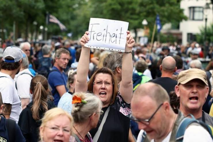 Berlin: O manifestanta agita o pancarta pe care se poate citi  'libertate' în cadrul unui protest împotriva pasaportului vaccinal si a obligativitatii vaccinale anti-Covid, 1 august 2021.