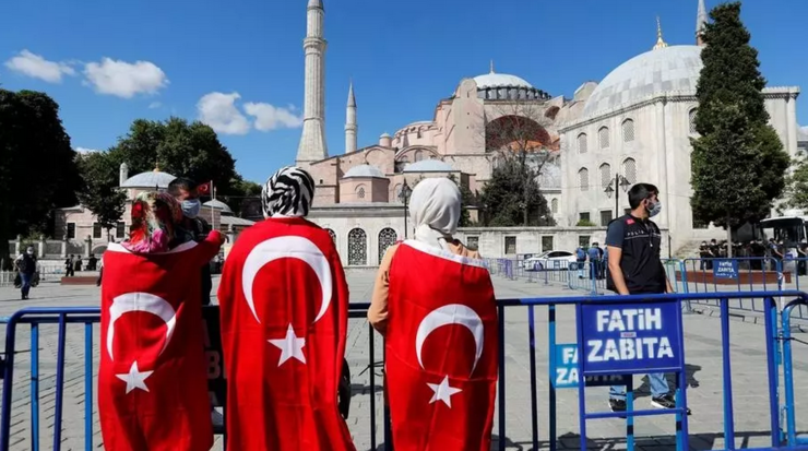 Persoane arborînd drapelul turc în apropiere de Bazilica Sfînta Sofia, 10 iulie 2020.