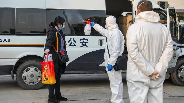 Un membru al personalului medical pulverizeazà dezinfectant pe un pacient la revenirea sa dintr-un spital într-o zonà sub carantinà la Wuhan, epicentrul epidemiei de coronavirus, 3 februarie 2020