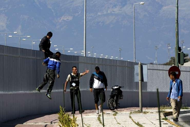 Un agent de securitate strigă la imigranţi afgani, care au sărit gardul unui terminal de feriboturi, în oraşul grec Patras (Foto: Reuters/Yannis Behrakis)