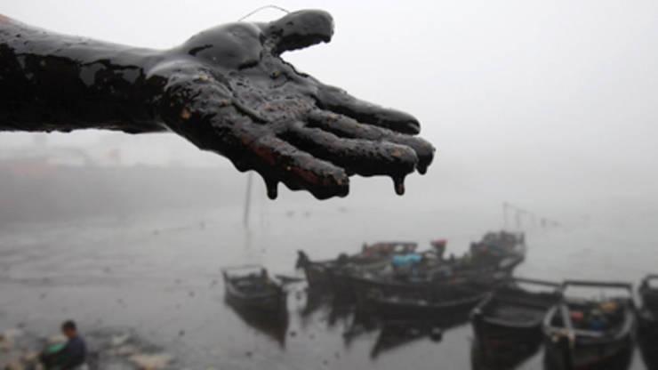 Mâna murdarà de petrol a unui muncitor care curàtà mareea neagrà de la Dalian, China, 21 iulie 2010.