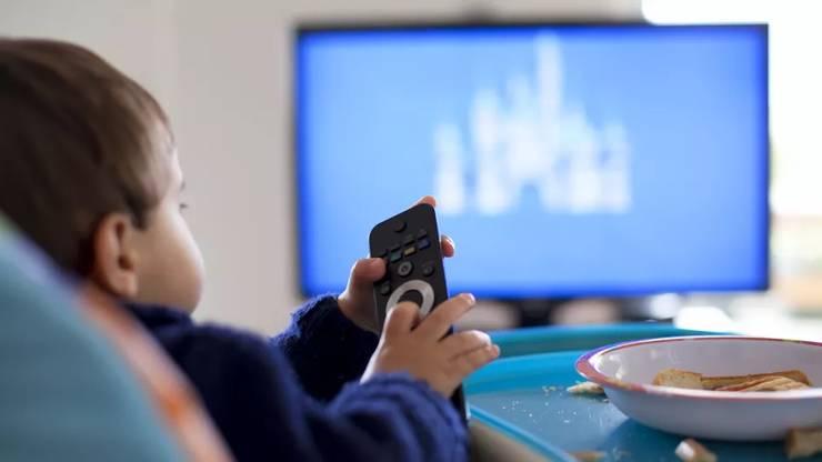 Un copil mâncând în fata televizorului (Fotografie de ilustratie).