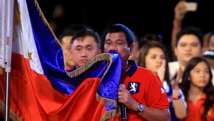 Rodrigo Duterte, presedintele-ales al Filipinelor, îmbràtisând drapelul national în cusrul unui miting electoral pe