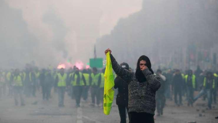 Un manifestant îsi tine vesta galbenà pe Champs-Elysées pe 24 noiembire 2018