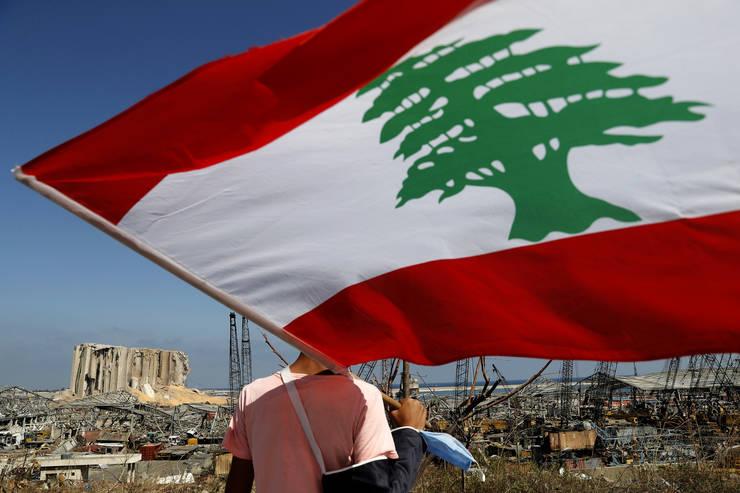 Un bărbat ține pe umăr drapelul Libanului, lângă zona exploziei din portul Beirut (Sursa: AP Photo/Hussein Malla/MEDIAFAX Foto)