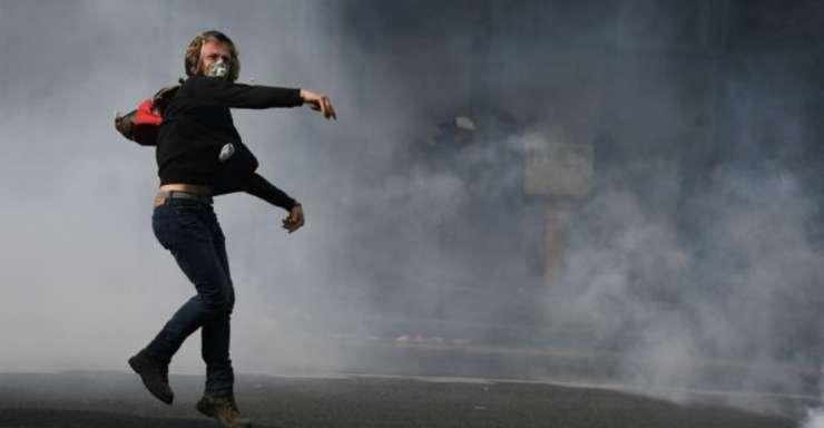Un manifestant din Paris aruncà proiectile contra fortelor de ordine care riposteazà cu gaze lacrimogene, 12 septembrie 2017