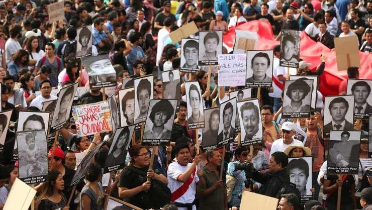 Manifestanti agita fotografiile victimelor fostului dictator Alberto Fujimori pentru a denunta eliberarea sa, Lima, Peru, 25 decembrie 2017