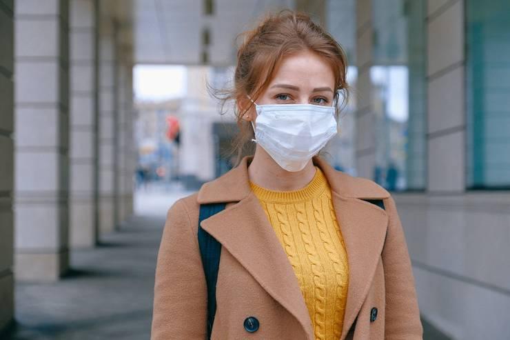 Femeie tanara pe strada cu masca sanitara pe nas si gura