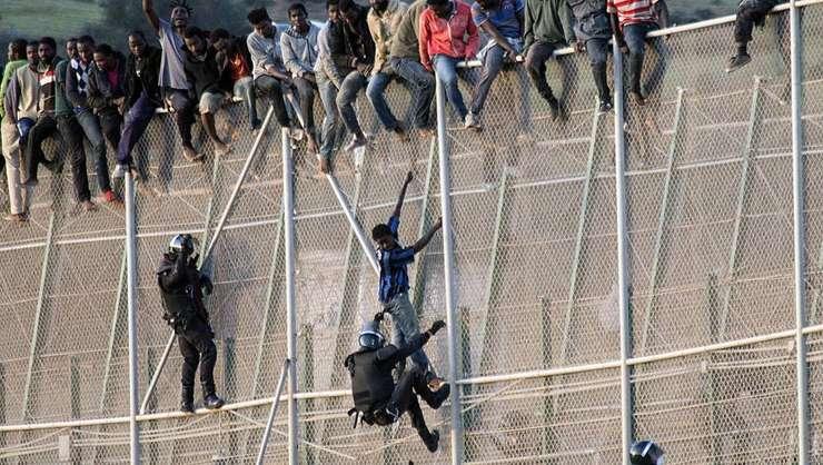 Politisti spanioli încercînd sa opreasca migranti doritori sa patrunda în enclava spaniola Mellila din Maroc.