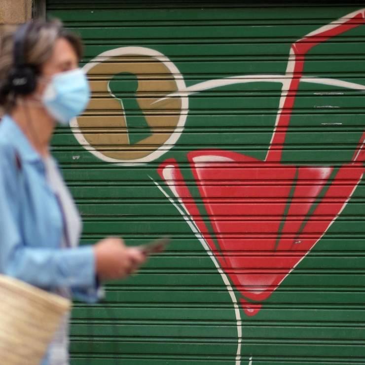 La Barcelona, o doamna poarta o masca sanitara pe strada, în aer liber. Guvernul a înasprit masurile sanitare pentru a diminua numarul de îmbolnaviri cu coronavirus.