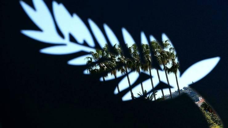 Palmierii din Cannes vàzuti prin emblema Festivalului de film.