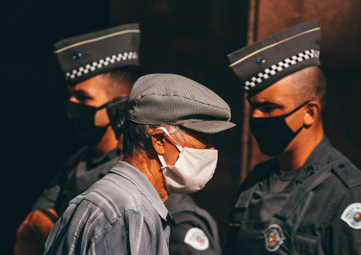 Persoana in etate cu masca din panza alba pe fata trece prin fata a doi militari cu masti sanitare negre pe fata
