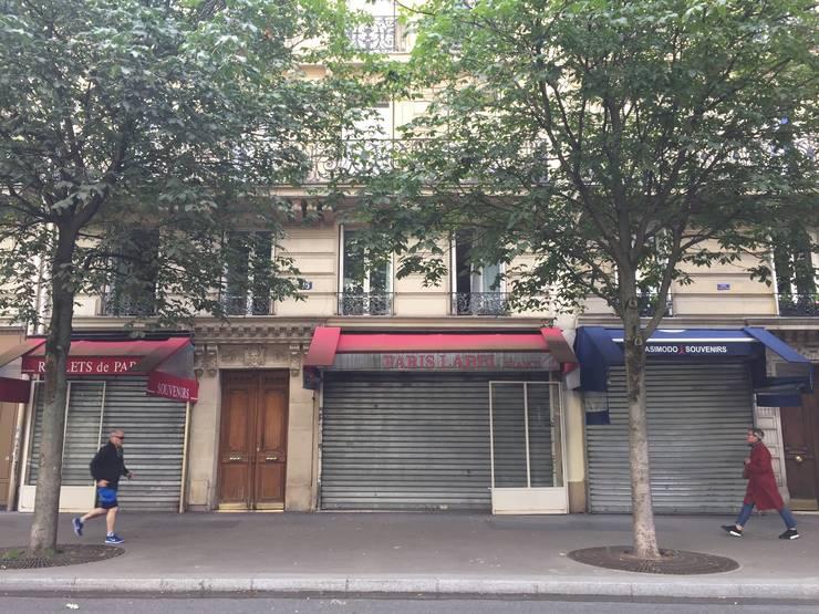 Pietoni trec pe lângă magazine închise situate într-unul din cele mai turistice cartiere din Paris, în apropiere de Notre Dame, iunie 2020.