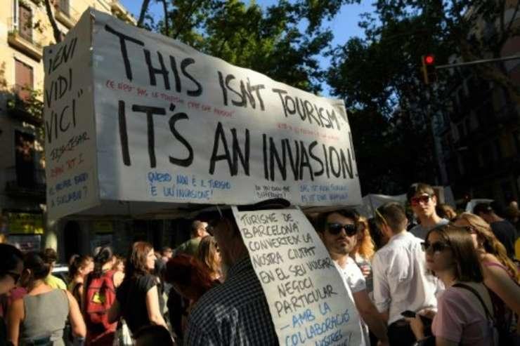 """Protestatari în Barcelona, 10 iunie 2017, purtând o pancarta pe care scrie """"acesta nu este turism este invazie"""""""