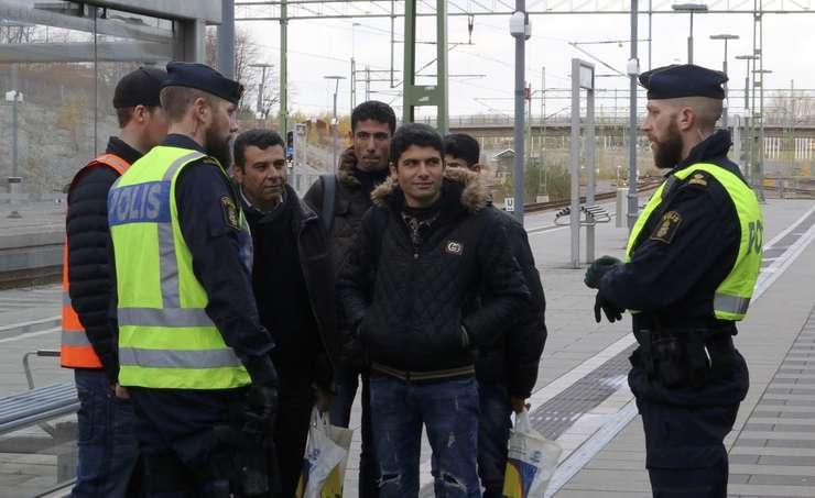 Politisti discută cu un grup de oameni la gara Hyllie, lângă Malmo (Foto: Reuters)