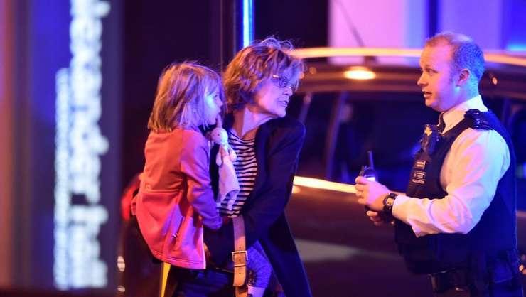 O femeie cu un copil în braţe discută cu un poliţist, după atacul de sâmbătă noapte din Londra (Foto: Reuters/Hannah McKay)