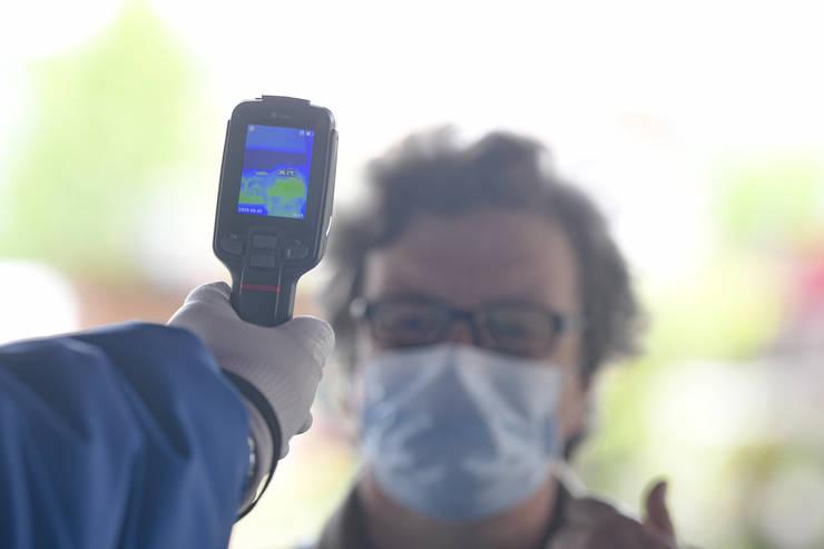 Un angajat al unei firme de pază măsoară temperatura clienților în piața Bucur Obor, joi, 7 mai 2020 (Sursa: MEDIAFAX FOTO/Andreea Alexandru)