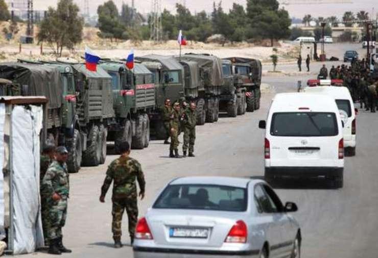 Soldati rusi si sirieni securizeazà convoaiele civililor evacuati de la Douma, din periferia capitalei Damasc, 12 aprilie 2018