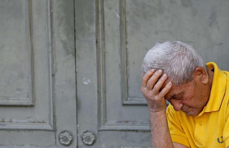 Un pensionar aşteaptă la intrarea unei bănci din Atena, pentru a-şi lua o parte din pensie (Foto: Reuters/Jean-Paul Pelissier)