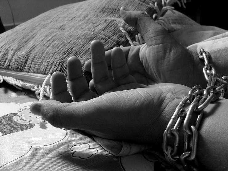 Imagine generica cu mainile legate ale unei victime a traficului de persoane. Fotografie alb-negru