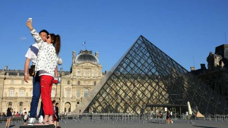 Turisti se pozeaza la Muzeul Louvre din Paris