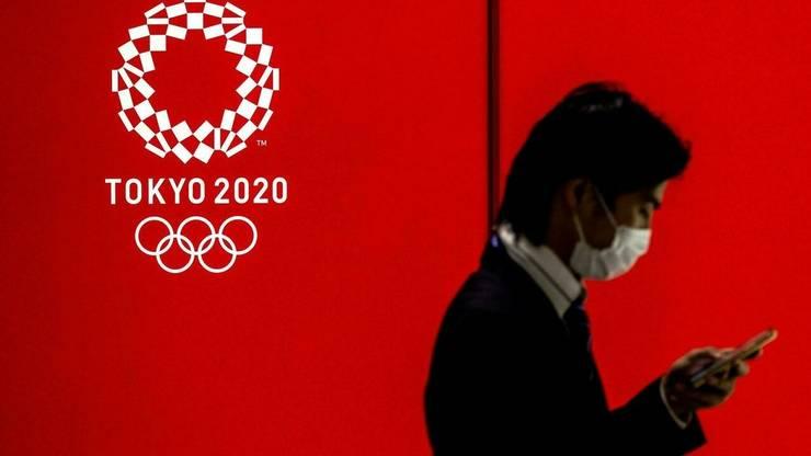 Un barbat ce poarta o masca sanitara poate fi observat lânga logo-ul Jocurilor Olimpice din Tokyo, pe 15 iulie 2021 în capitala japoneza.