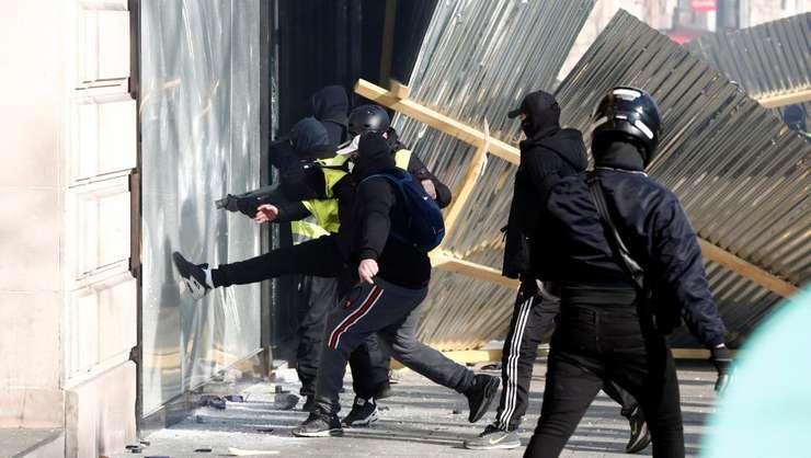 Un grup de black blocs distrug o vitrina în cadrul unei manifestatii la Paris.