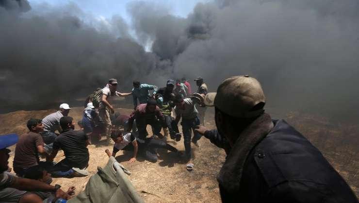 Un grup de palestinieni încearca sa ajute la evacuarea unui ranit, Gaza, 14 mai 2018