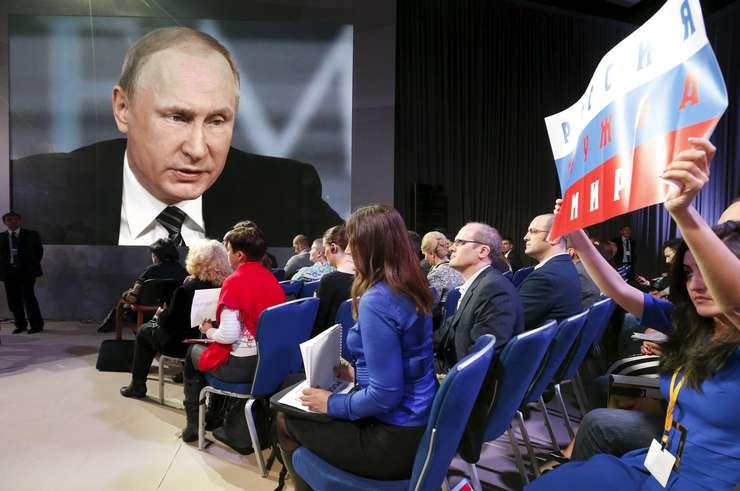 O jurnalistă ridică un banner, pentru a-i putea pune o întrebare preşedintelui rus, Vladimir Putin (Foto: Reuters/Sergei Karpukhin)