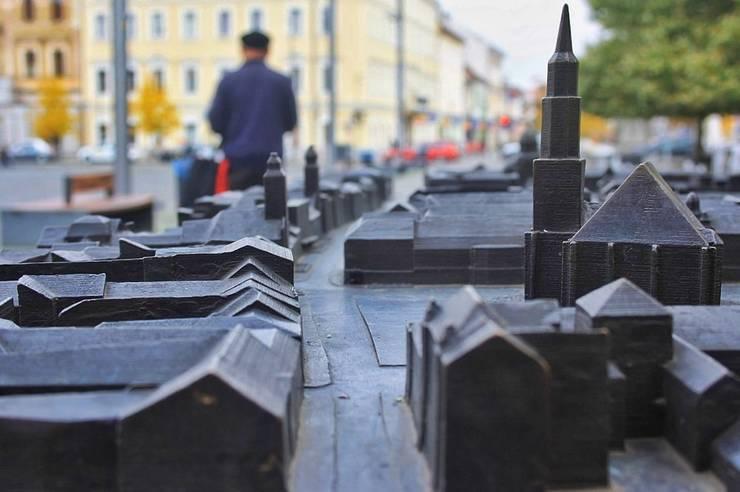 O hartă în relief pentru nevăzători situată în Piața Uniriii cu orașul Cluj-Napoca, iar în spatele hărții un om care merge