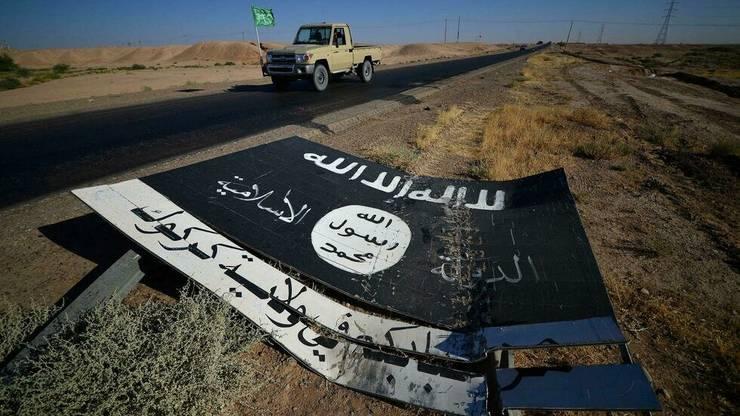 Un drapel al organizatiei stat islamic pe drumul bazei militare Al-Fatiha, la sud de Hawija, Irak, 2 octobrie 2017.