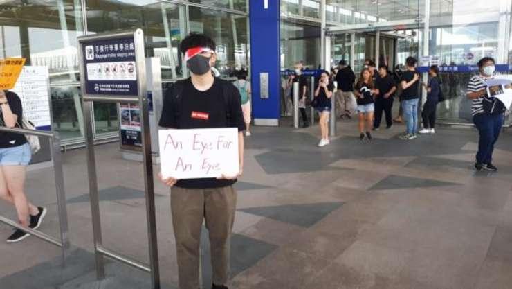 'Ochi pentru ochi' se poate citi pe pancarta tinuta de un tânar protestatar pro-democratie, aeroportul din Hong Kong, 13 august 2019.