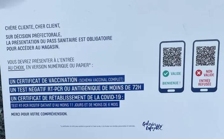 Afisul de la intrarea în Galeries Lafayette, luni 9 august 2021.