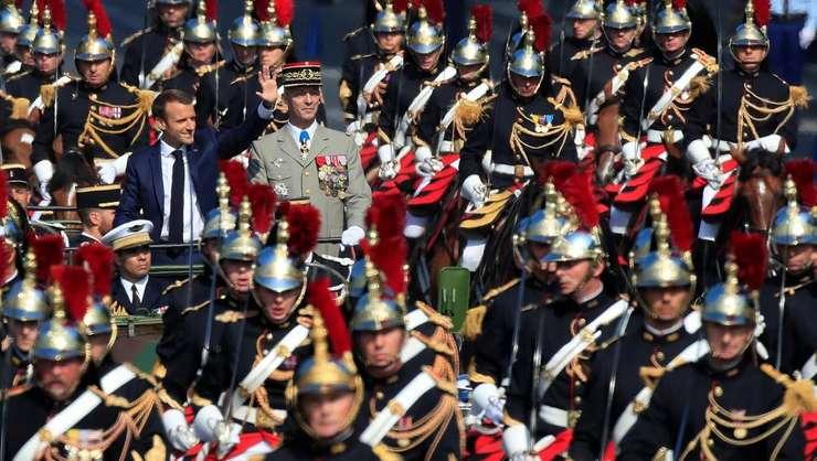Presedintele Emmanuel Macron traverseaza Champs Elysées alturi de seful de stat-major, generalul François Lecointre. Ei sunt flancati de Garda republicana.