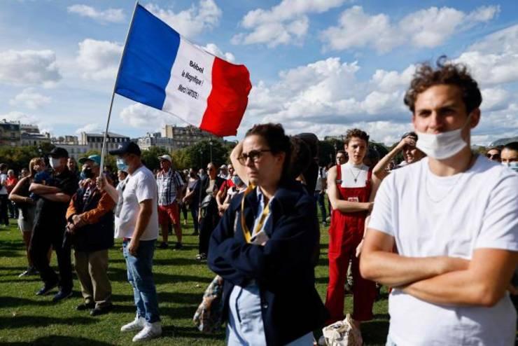 """Un fan al lui Jean-Paul Belmondo flutura un steag albastru-alb-rosu ca omagiu adus lui """"Bébel Le Magnifique, merci L'Artiste!"""", Invalides, 9 septembrie, Paris."""