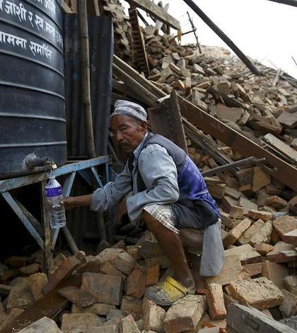 Un bărbat ia apă dintr-un rezervor, lângă ruinele unui templu prăbuşit la Kathmandu (Foto: Reuters/Navesh Chitrakar)