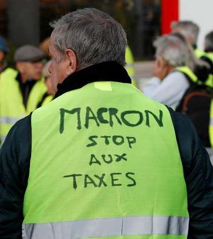"""Un protestatar din miscarea """"Vestele galbene"""". Pe vesta lui se poate citi 'Macron, opreste taxele'."""